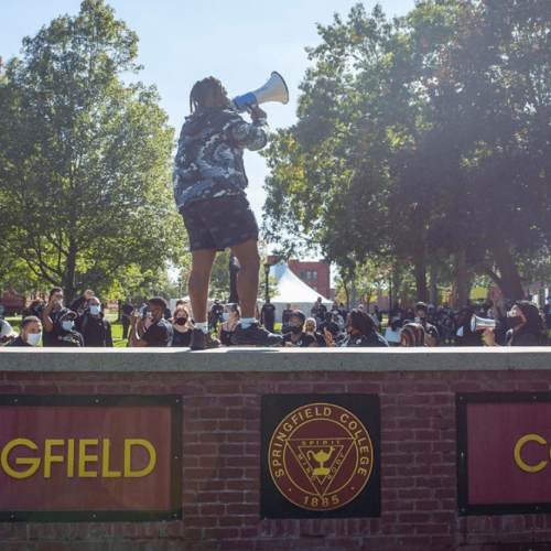Student with a megaphone on the Springfield College sign during March for Action on Alden