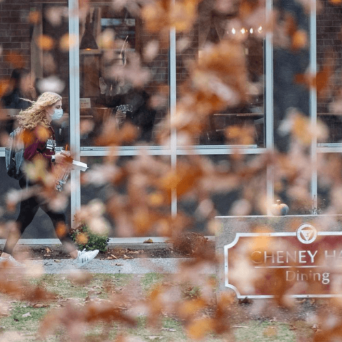 A blizzard of leaves while a student walks by Cheney in the background.