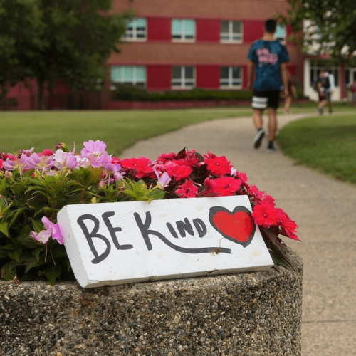 A Be Kind sign on a planter on campus with a student in the background.