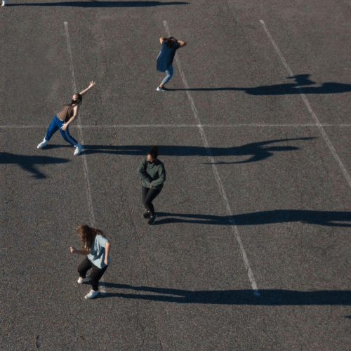 Aerial view of dancers practicing in a parking lot