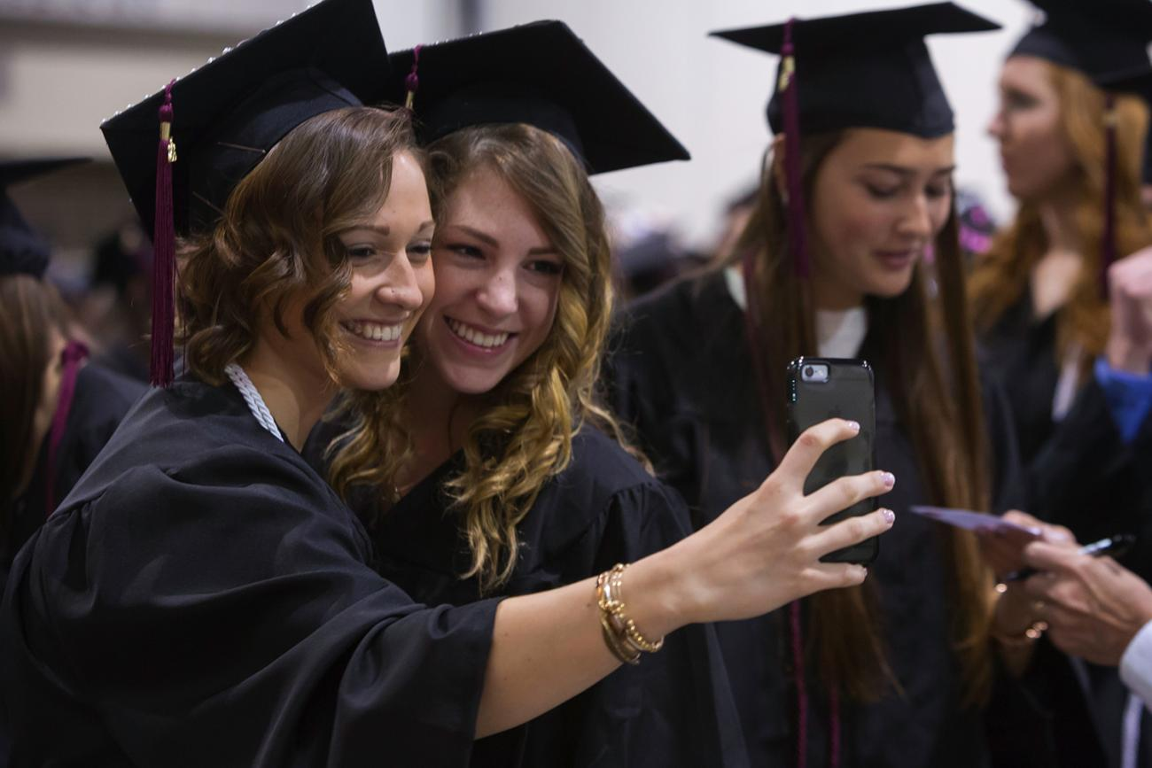 Two female students take a selfie at Springfield College commencement in 2016