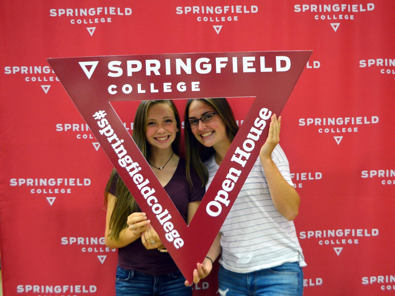 Two female students pose in a triangle cut out during open house.