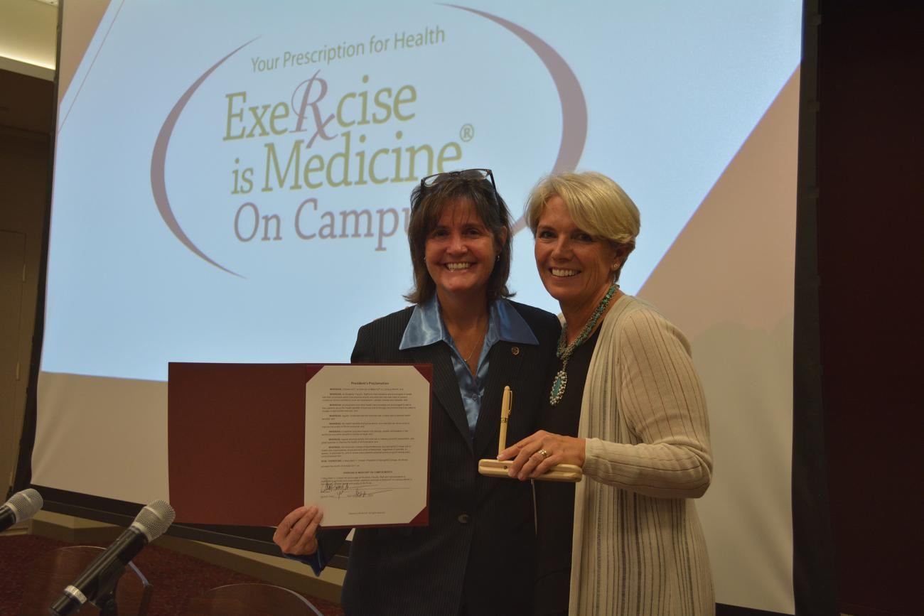 As part of the Joint Speaker Series, Springfield College President Mary-Beth Cooper, right, proclaims October as Exercise is Medicine on Campus month with a special proclamation ceremony with Springfield College Department of Exercise Science and Sport Studies Chair Dr. Sue Guyer.
