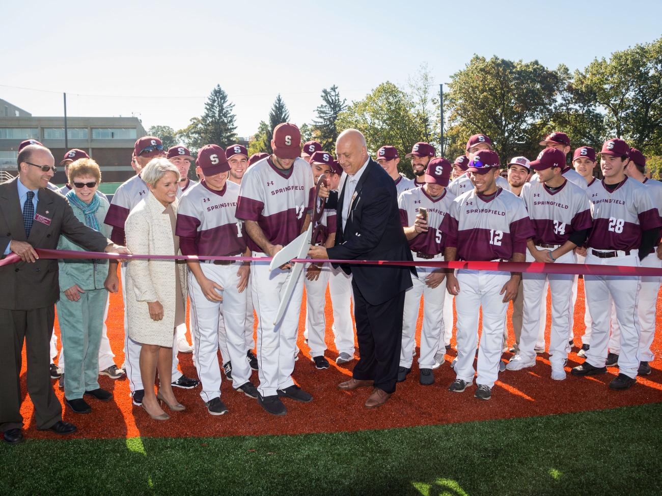 The Springfield College Men's baseball team, college leaders, and Cal Ripken Jr. join together to cut the ribbon on the new adaptive field.