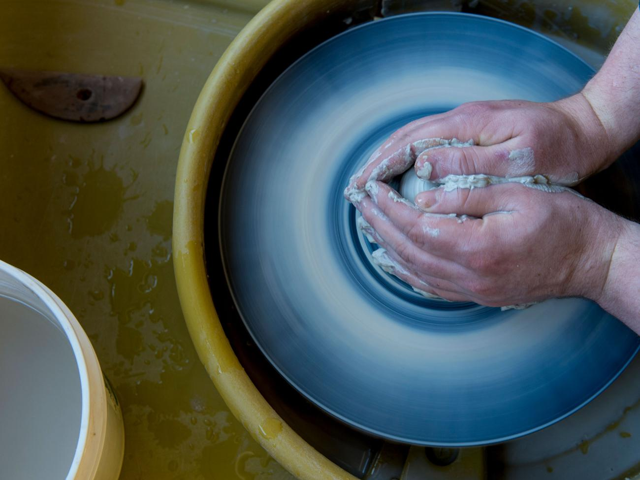 A pair of hands sculpting a clay bowl in the art studio.