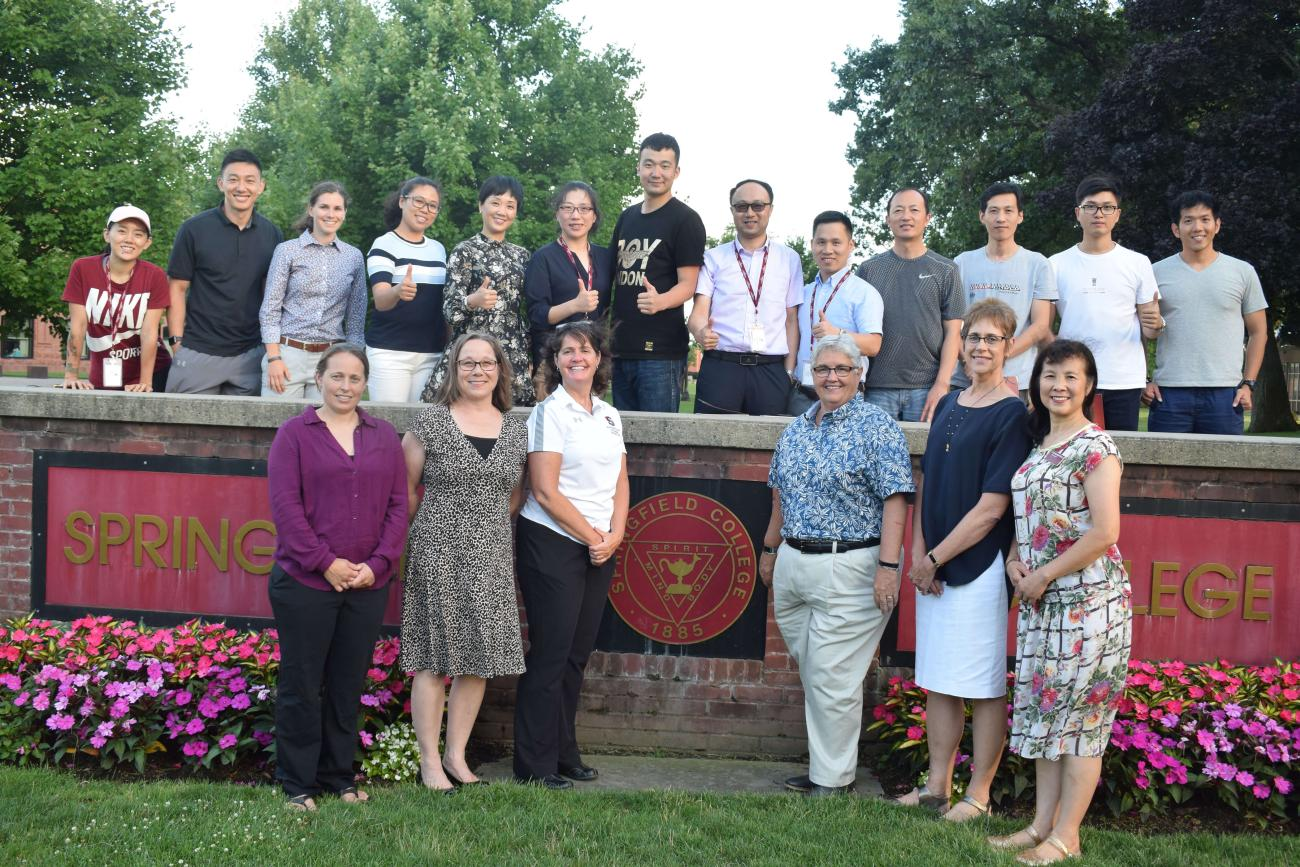 Springfield College faculty and visiting Chinese instructors pose before the college sign