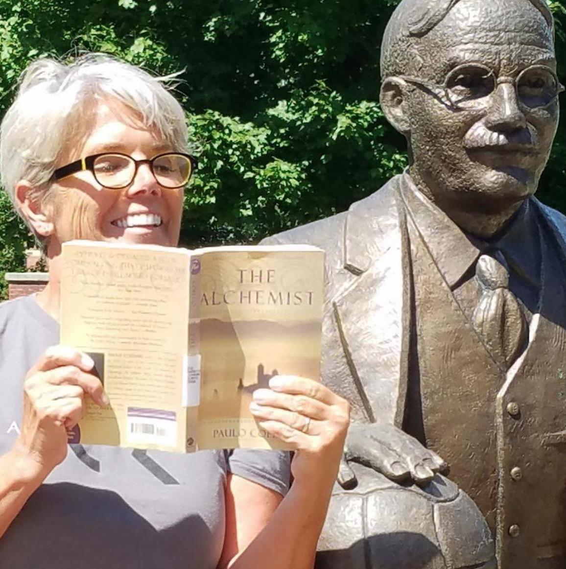 President Mary Beth Cooper reads Paulo Coelho's The Alchemist while sitting next to the James Naismith statue.
