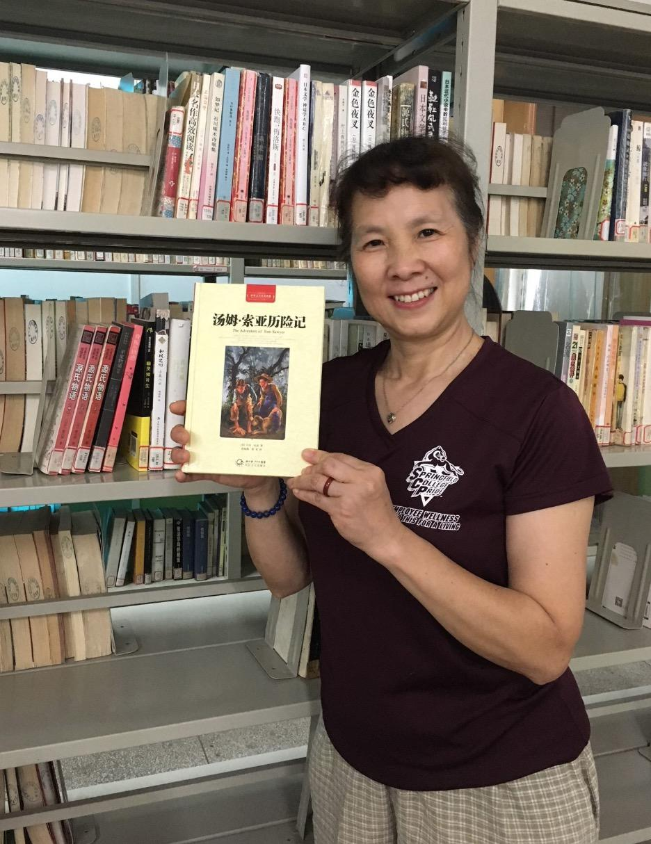 Cathy Xu holds a copy of Tom Sawyer in her native Chinese language.
