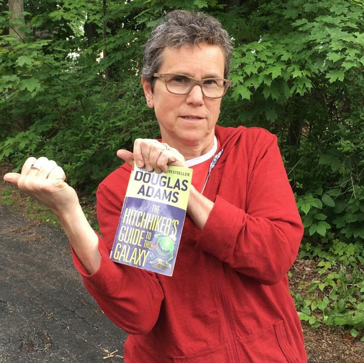 Julia Chevan jokingly hitchhikes while holding a copy of Hitchhikers Guide to the Galaxy