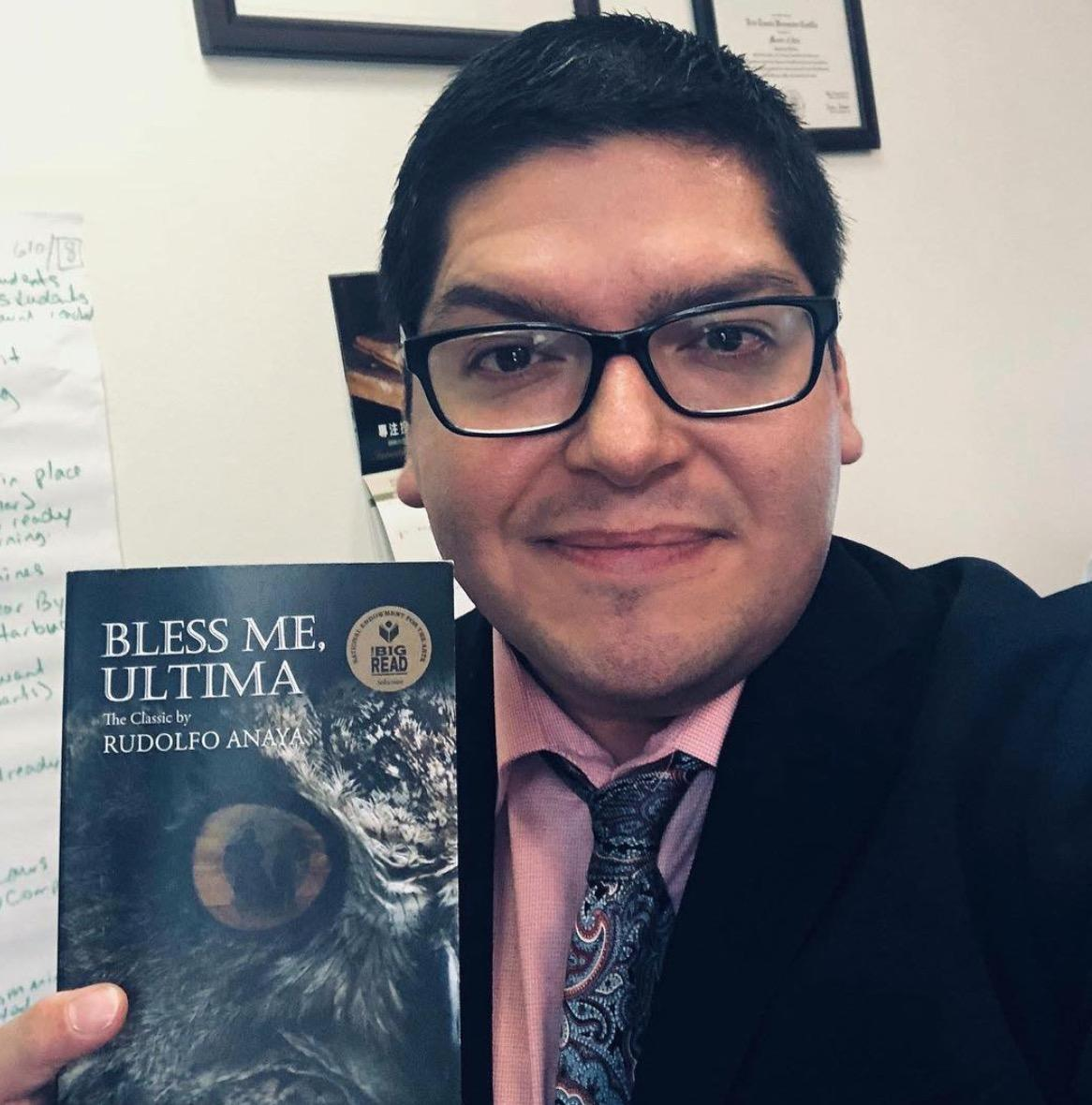 Eric Castillo hold a copy of Bless Me, Ultima