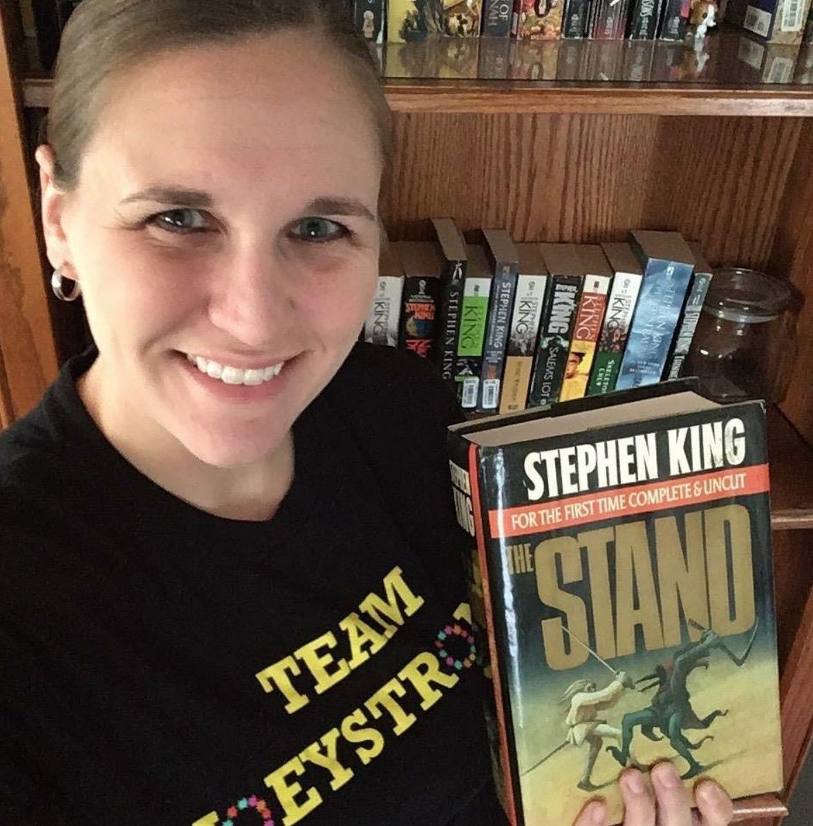 Outreach Librarian Kerri Vautour holding a copy of Stephen King's The Stand.