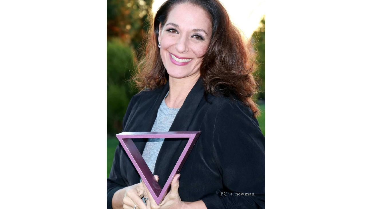 Marianna Newman holding a triangle.