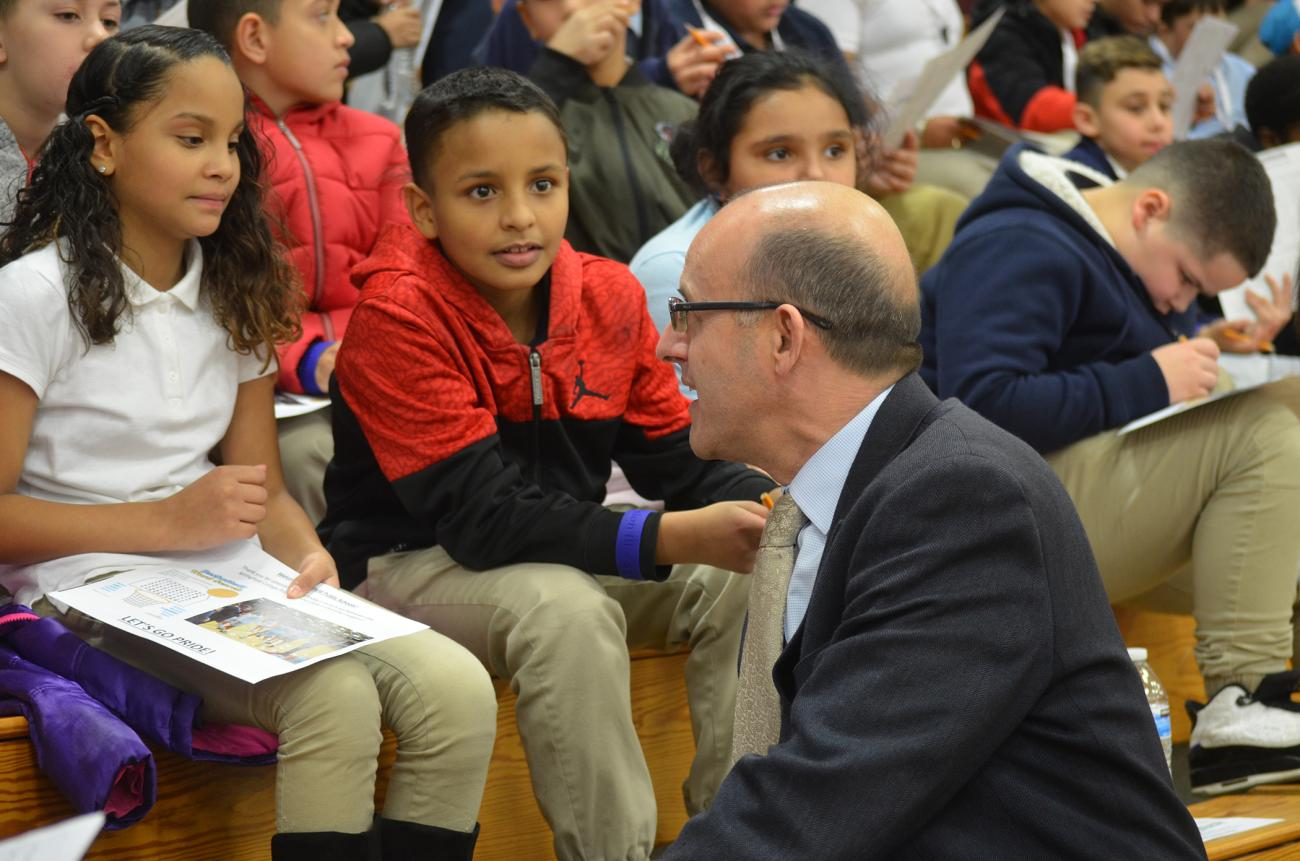 Springfield College Athletic Director Craig Poisson talks with youngsters from local Springfield elementary schools.