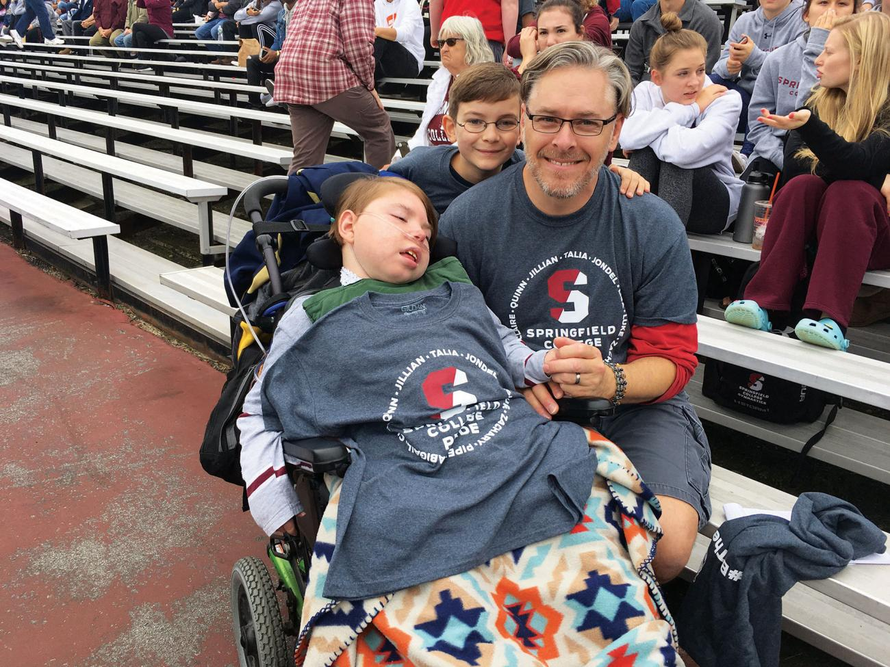 Team IMPACT participant and Men's Gymnastics teammate Zachary LaBroad and his father Eric Volz Benoit attend a Pride football game.