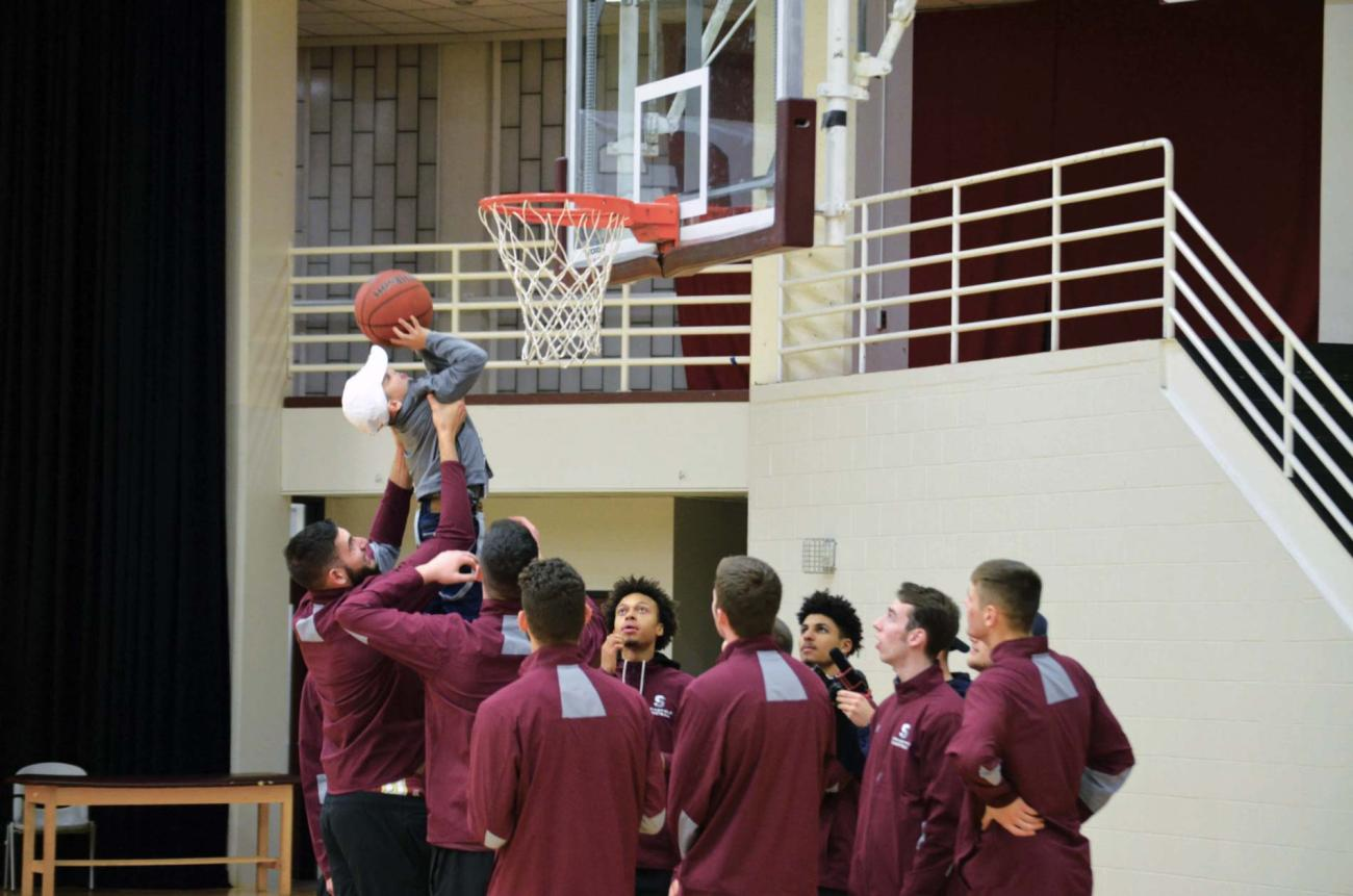 Jondel Rivera Ruiz gets a hand making a basket from the Springfield College Men's Basketball