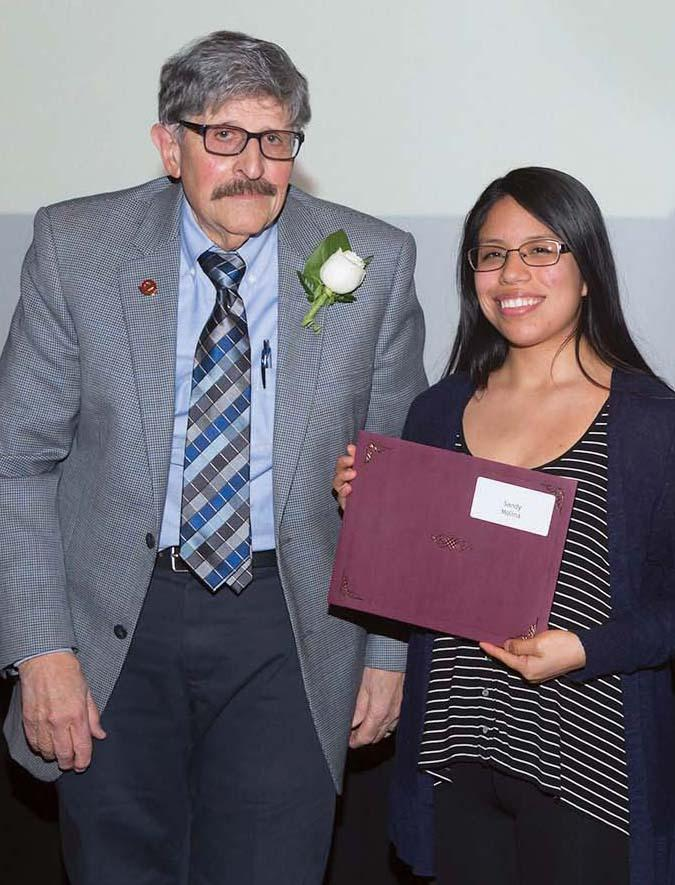 Springfield College Emeritus Professor Peter Polito, left, presents a Friends in Humanics Scholarship.