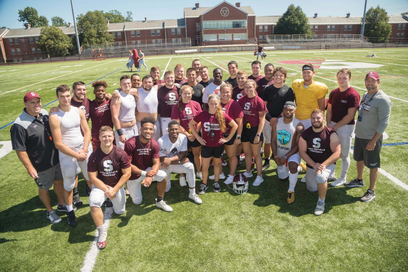 Springfield College Football strength and conditioning coaches at center from left, Izabella Mocarski, Kellie Gambell, Olivia Indorf, and Terrie Bradshaw with players and coaching staff