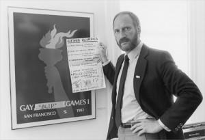 Tom Waddell stand next to the Gay Games poster in 1980s