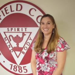 Photo of Joy Erickson in front of Springfield College seal.