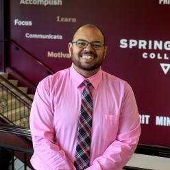 A photo of Robert Gordon, smiling, standing in front of a wall with the Springfield College logo on it