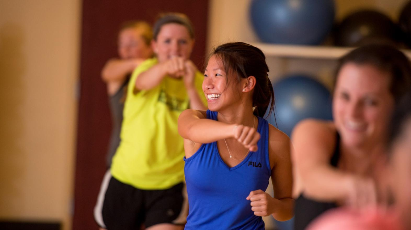 Female students smile as they work out in a group exercise class at Springfield College