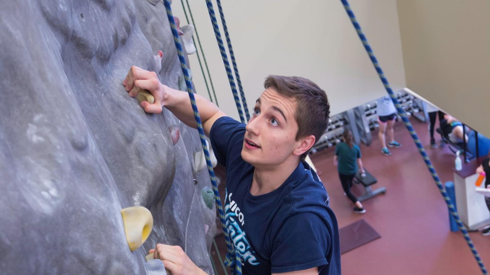 Male student using the climbing wall in Springfield College Wellness Center