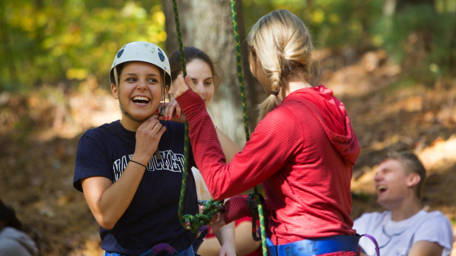Female students laugh as they participate in the challenge course at East Campus