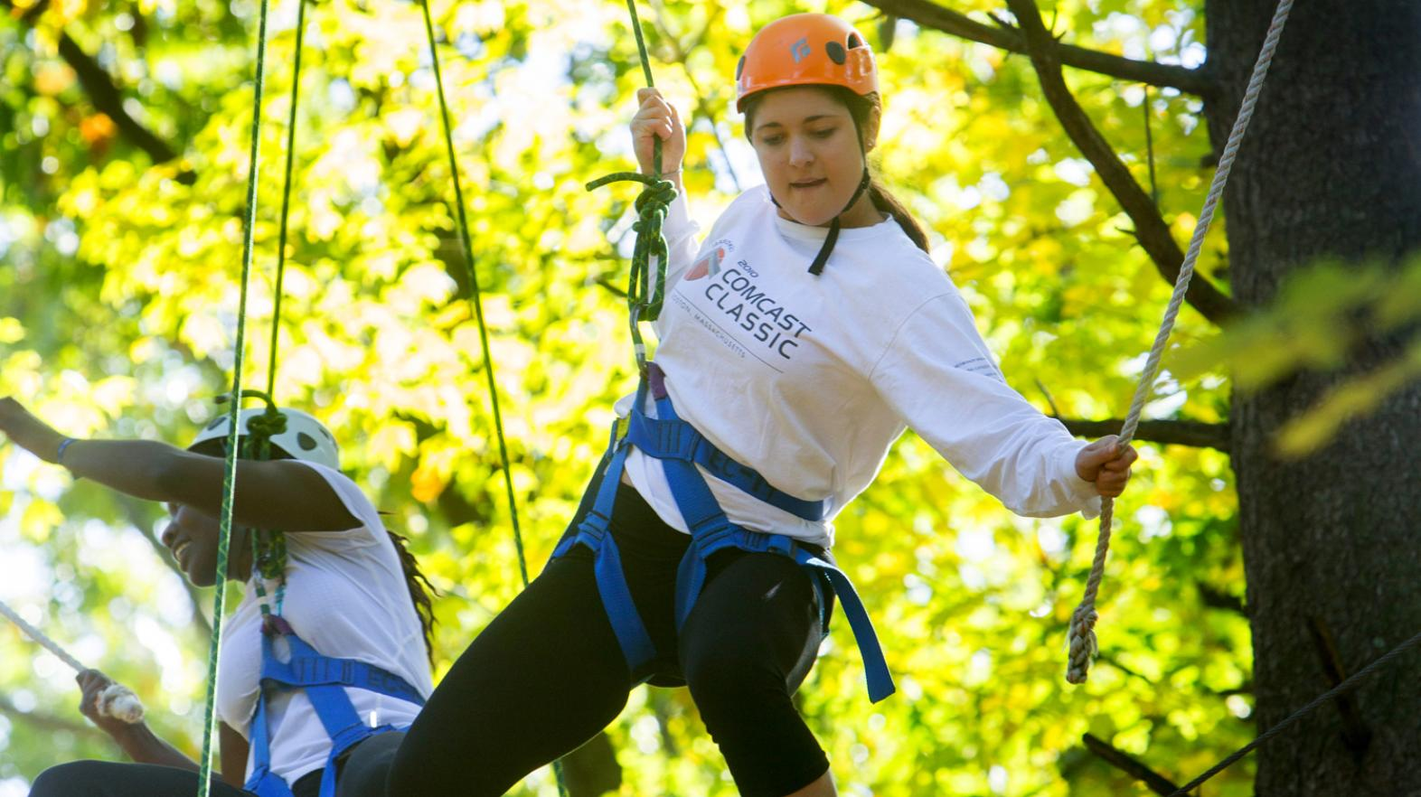 Female students in a tree as they navigate the challenge course at East Campus