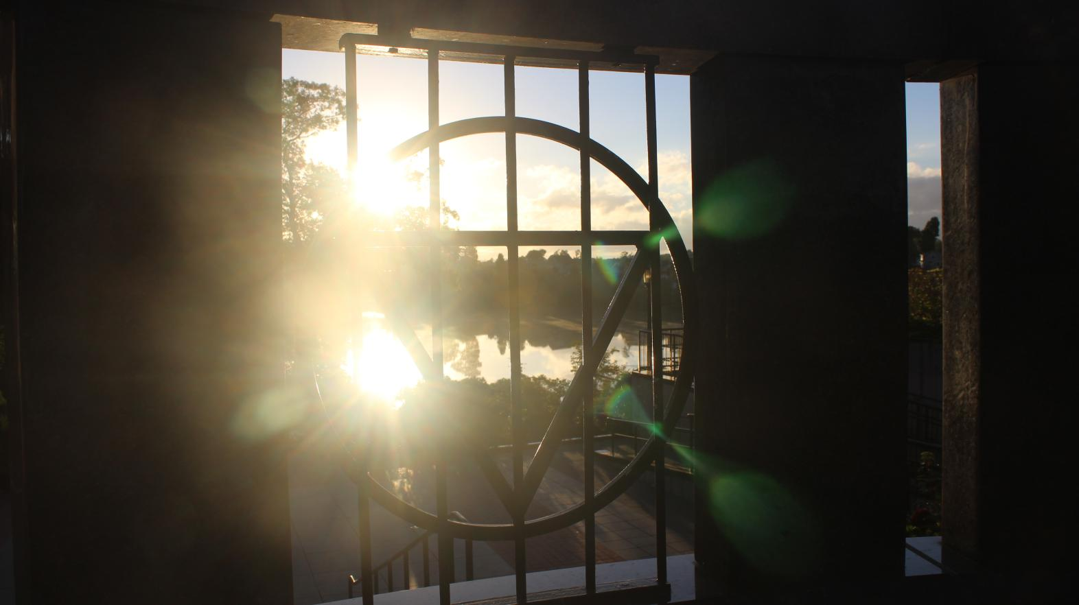 Our Gulick triangle frames the sun rising over Lake Massasoit in this photograph from graduate student Paige Moran.