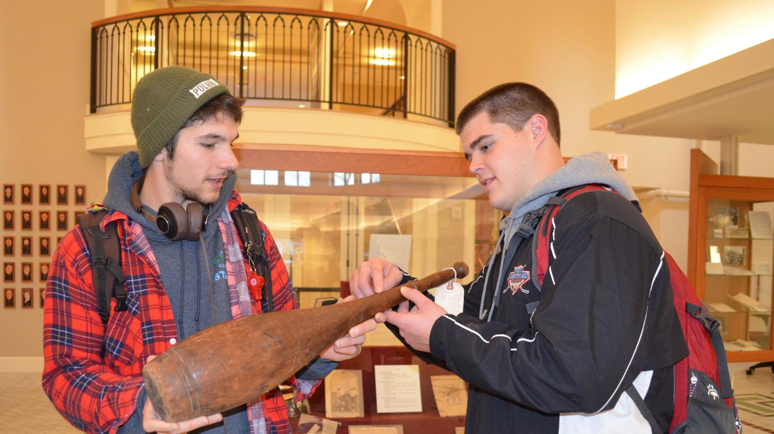 Two students examine a historic piece of pottery in the Springfield College experience.