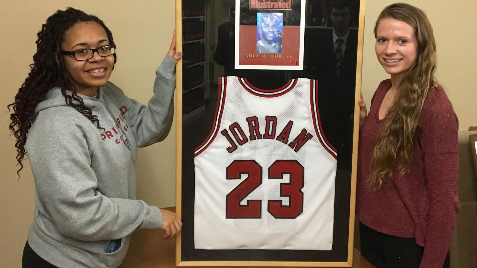 Students pose with a framed Michael Jordan Jersey, located in the Springfield College archives.
