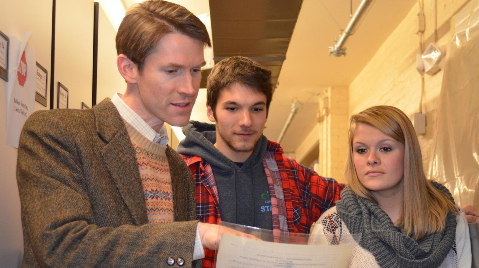Professor Tom Carty looks at James Naismith's Springfield College application with two students.
