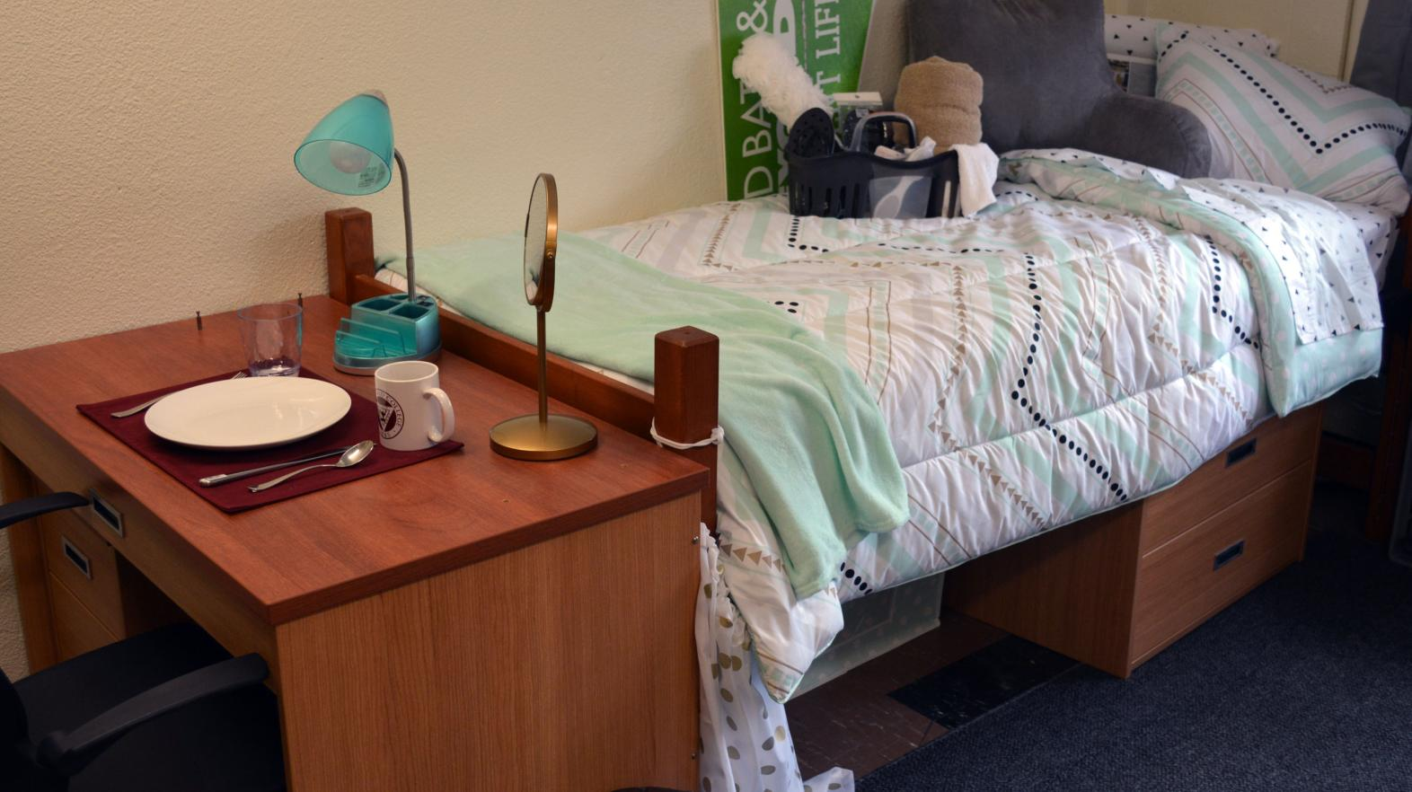 A desk with a plate on it and a bed in Massasoit Hall.