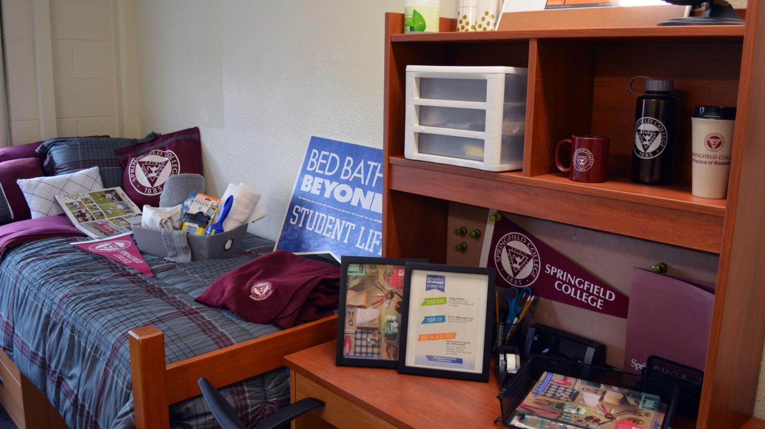 A Massasoit Hall residence room with bed and desk adorned with Springfield College gear.