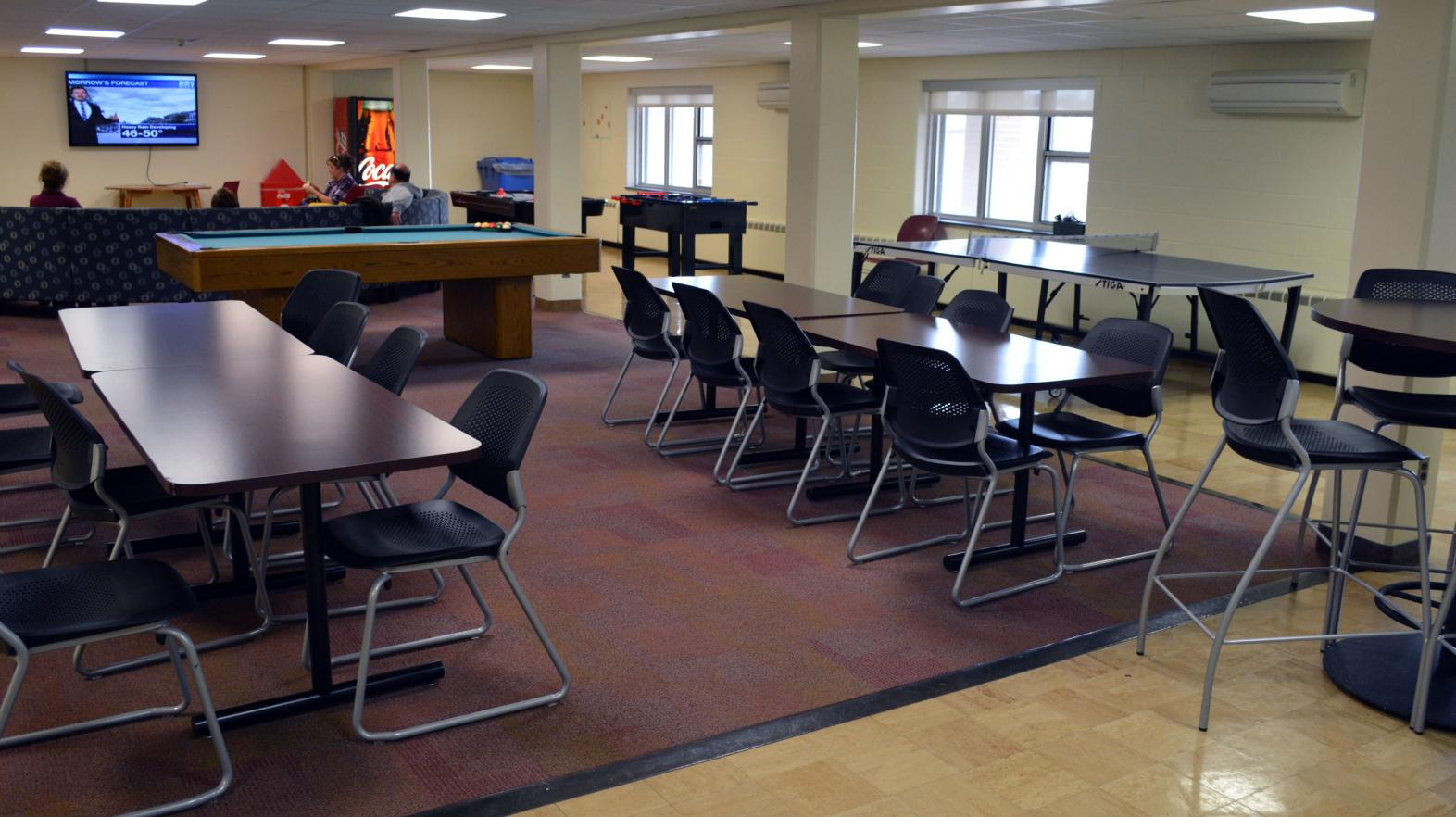 The common area in Massasoit residence hall, complete with dining area and TV area.