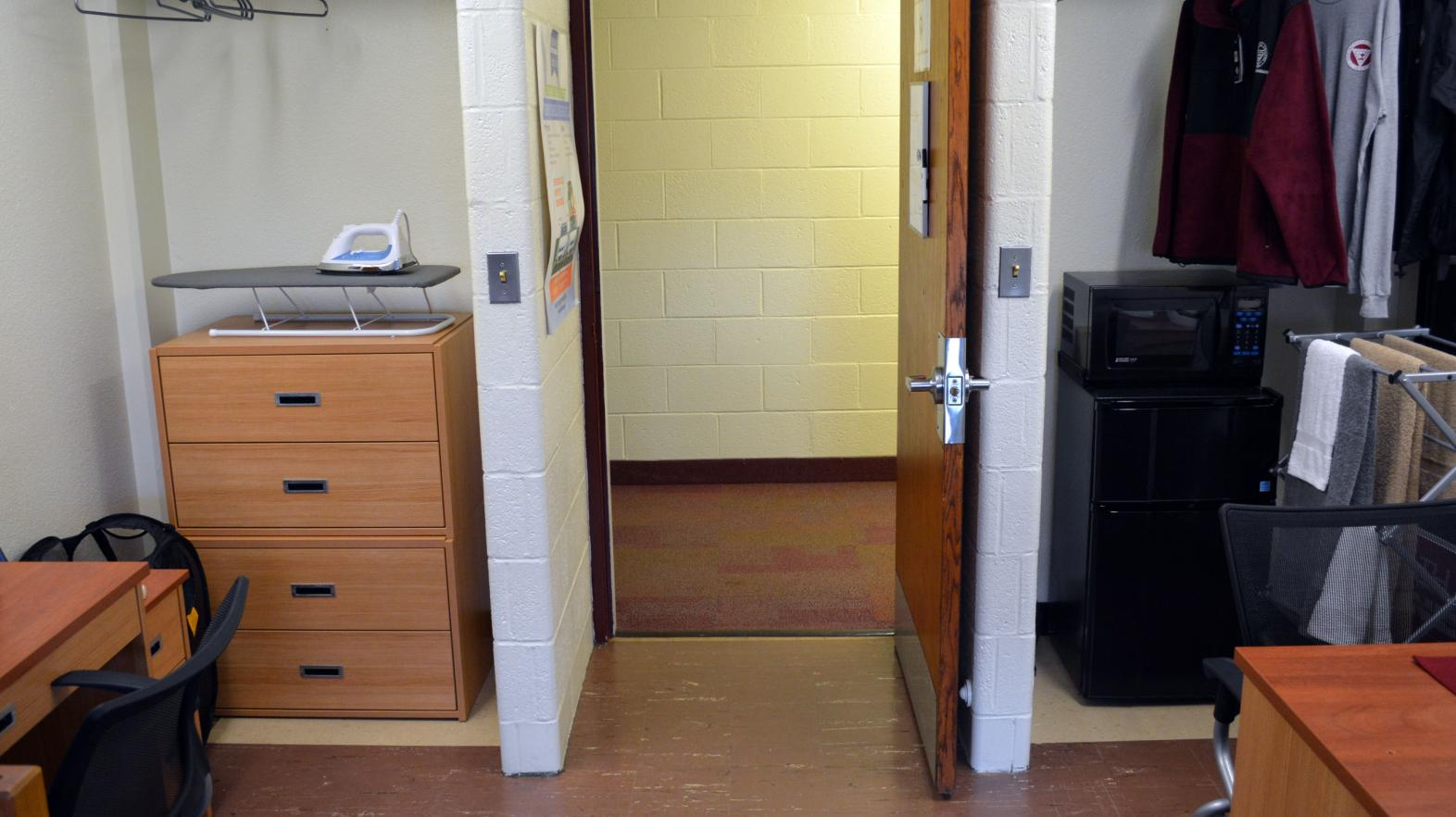 Massasoit Hall room with an open door and closet to show the community feel created in the residence hall.