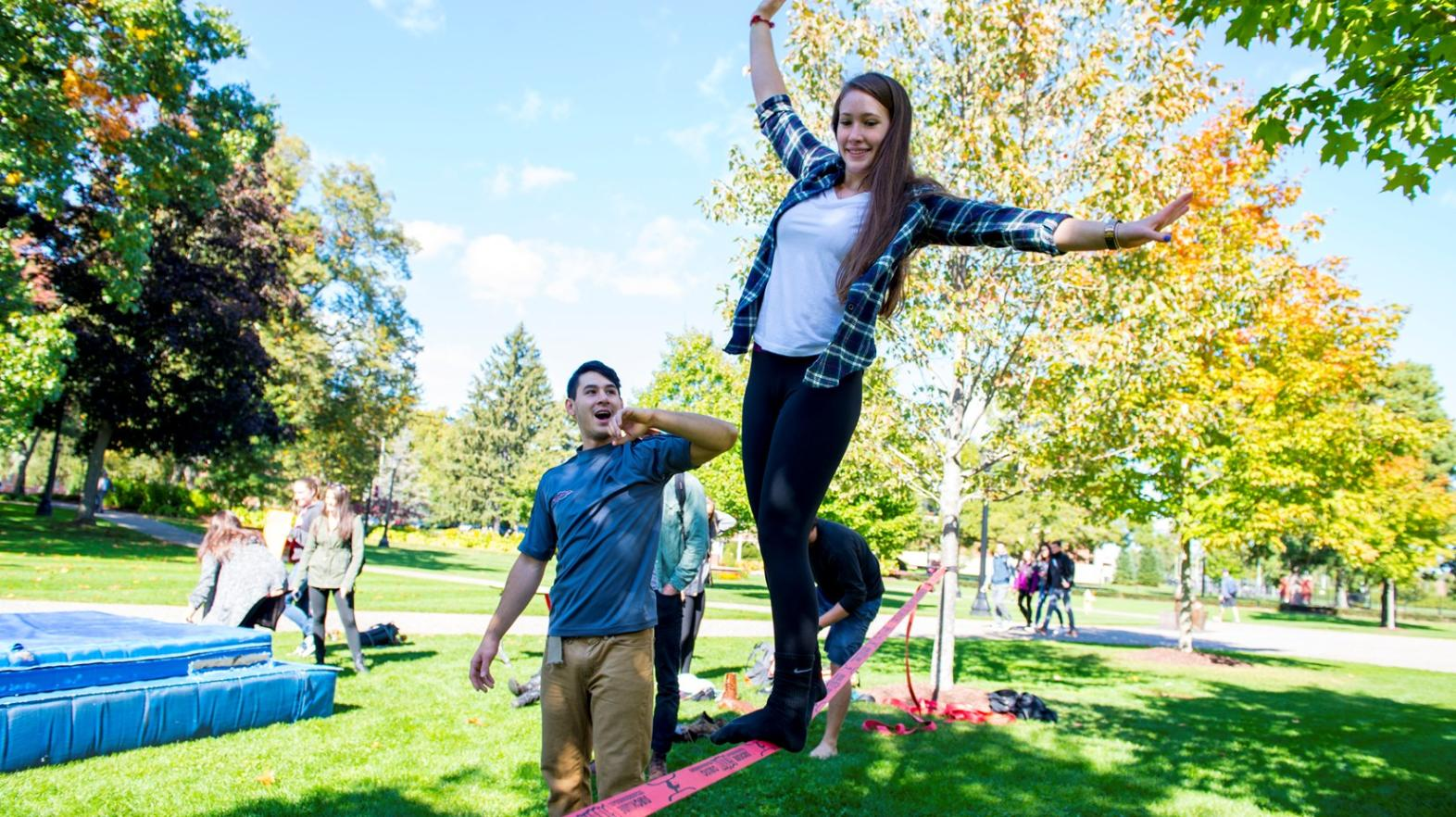 Springfield College students on the green walk on a tight rope