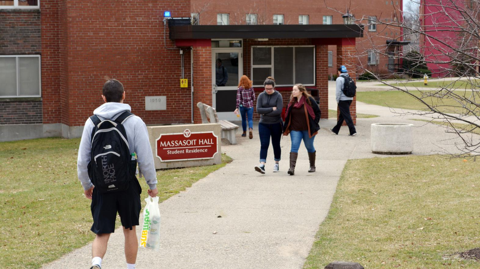 The front of Massasoit Hall with students walking into the building.