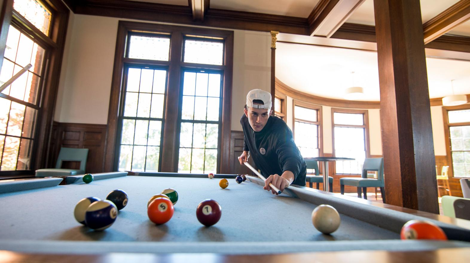 A student plays pool in Carlisle Foyer in the Alumni Hall residence hall.