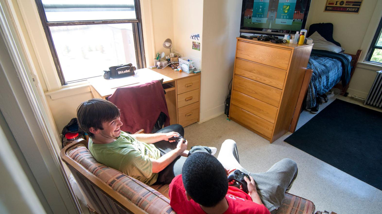 Two students laugh with eachother while playing video games in their residence hall room.