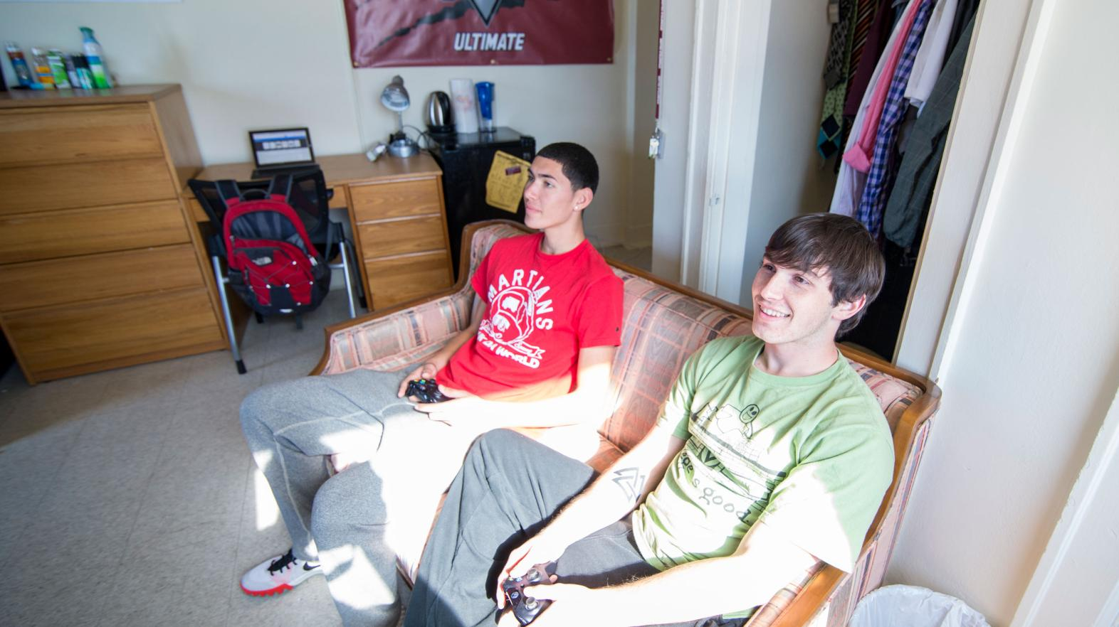 Two students play video games in their Alumni Hall dorm room.