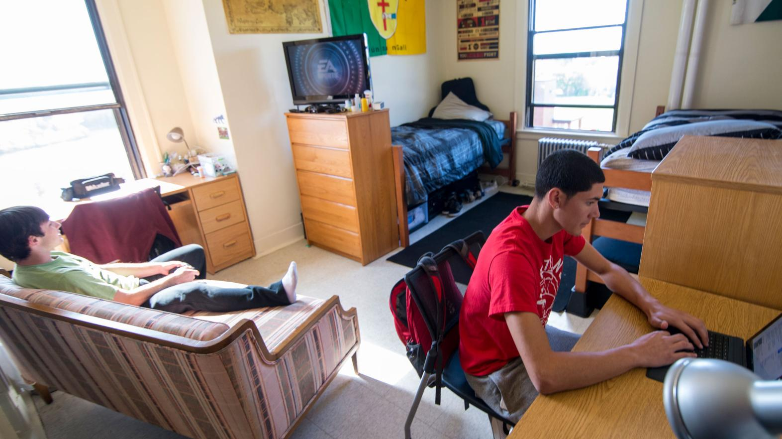 A student sites at his desk to work on his laptop while his roommate plays video games in their residence hall room.
