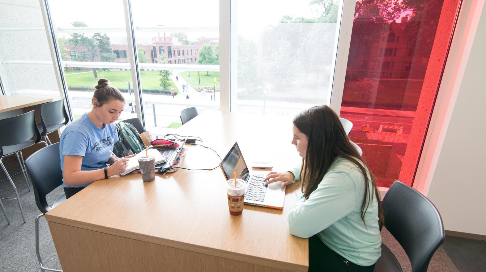 Two female students study at a table in the Learning Commons