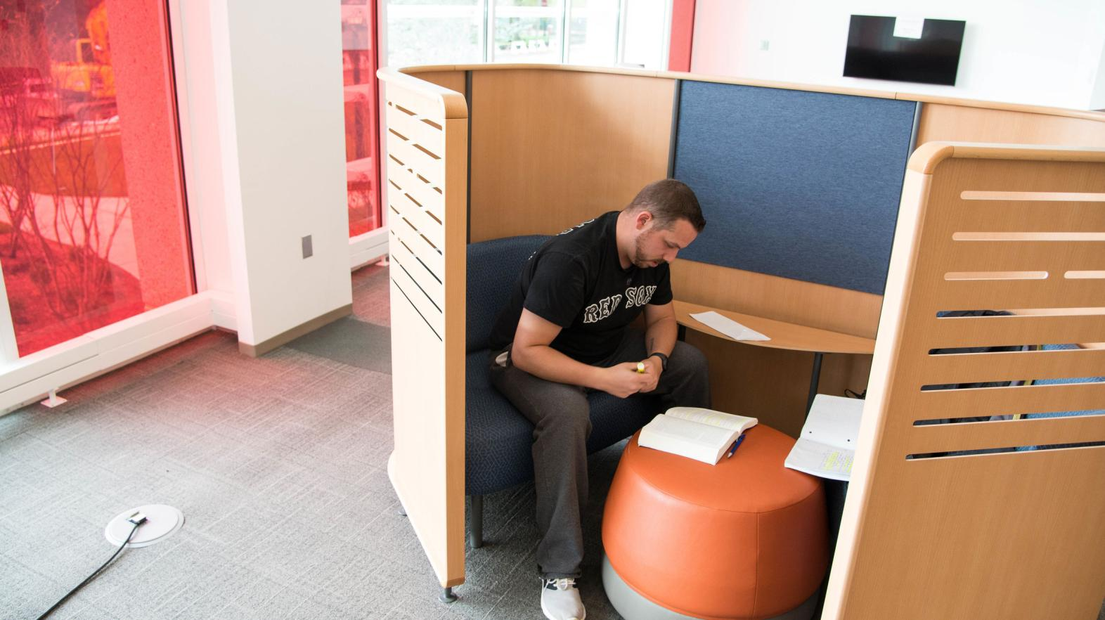 A male student studies in a study nook in the Harold C. Smith Learning Commons.