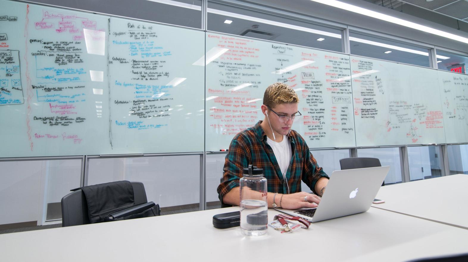 A male student types on his laptop as he sits in front of a white board with notes written on it.