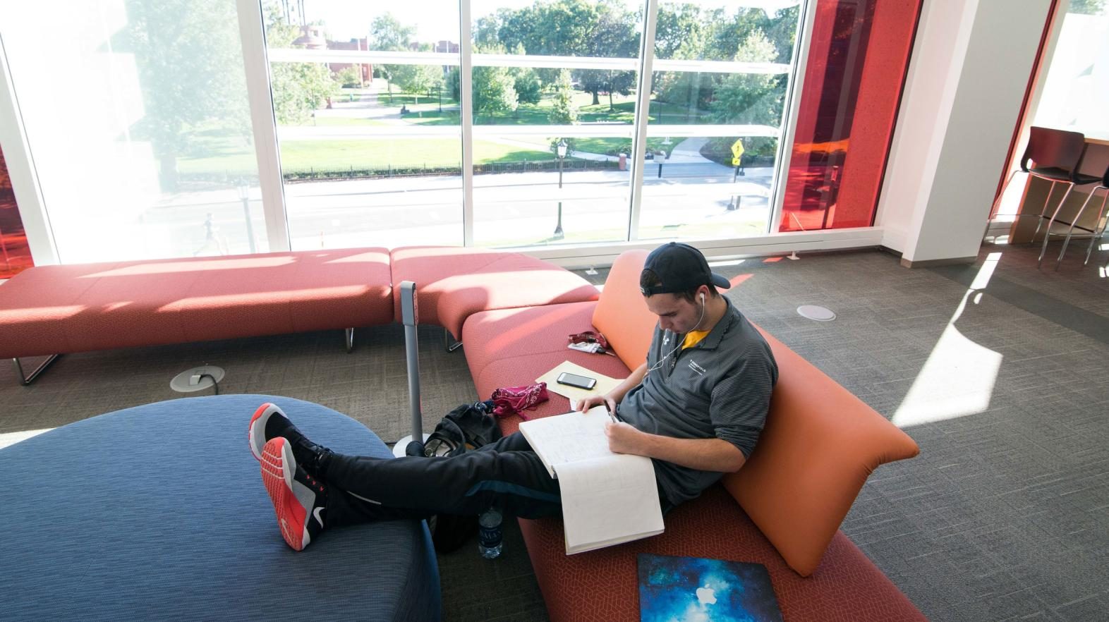 A male student reads from his notebook on a couch in the Learning Commons.