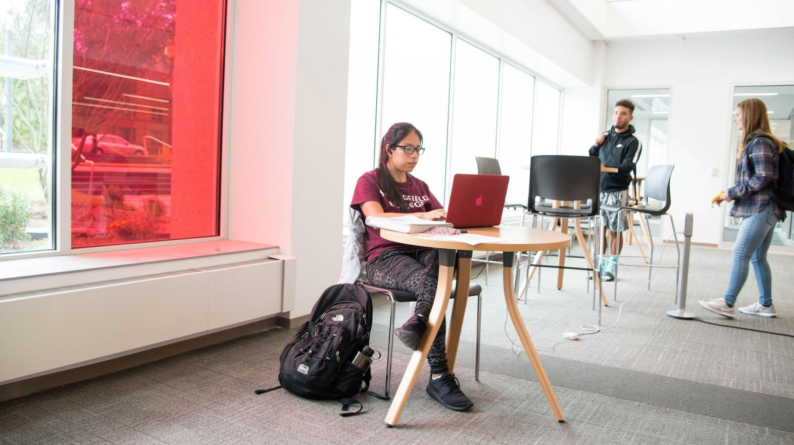 A female student types on her laptop in the Learning Commons.