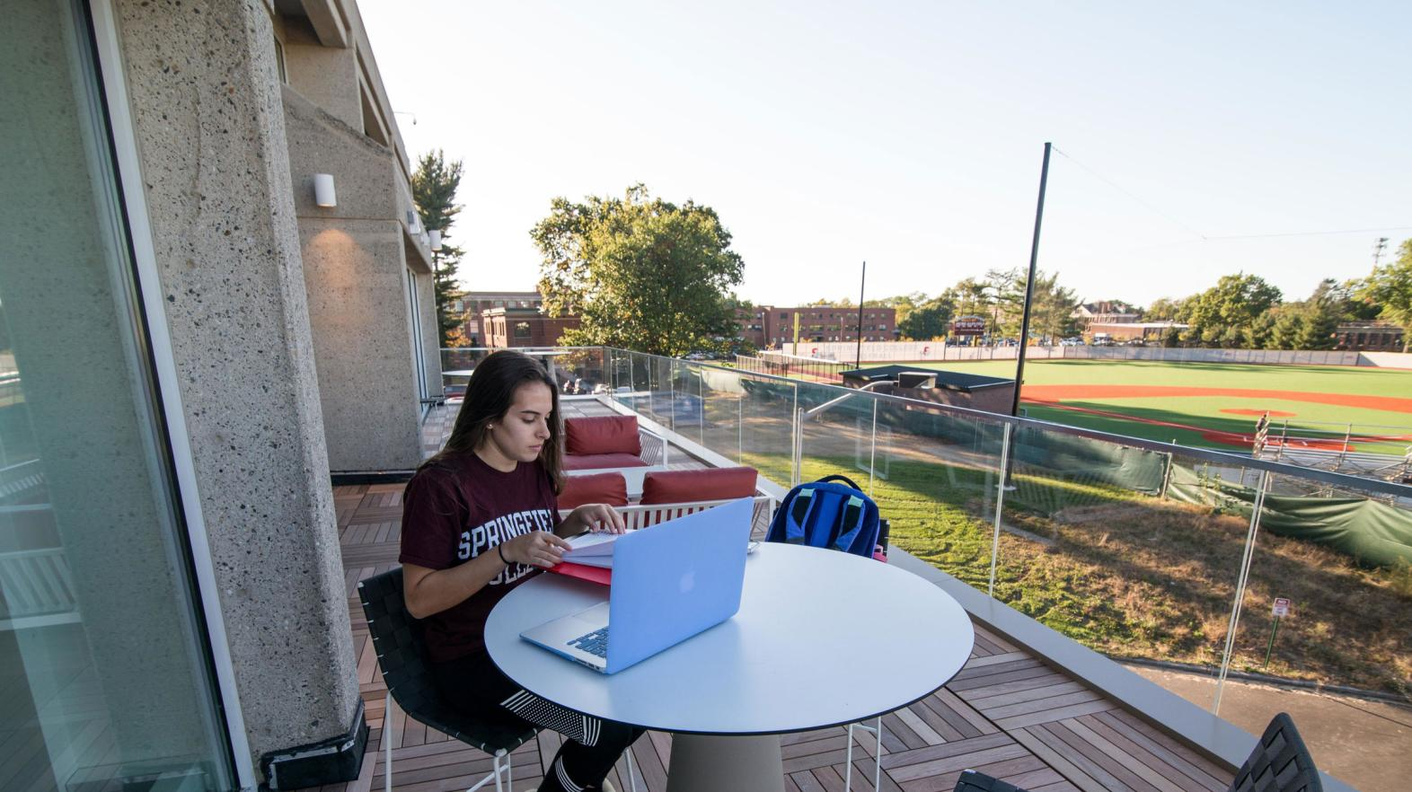 A female student works on her laptop outdoors on the Cooper Terrace of the Learning Commons.