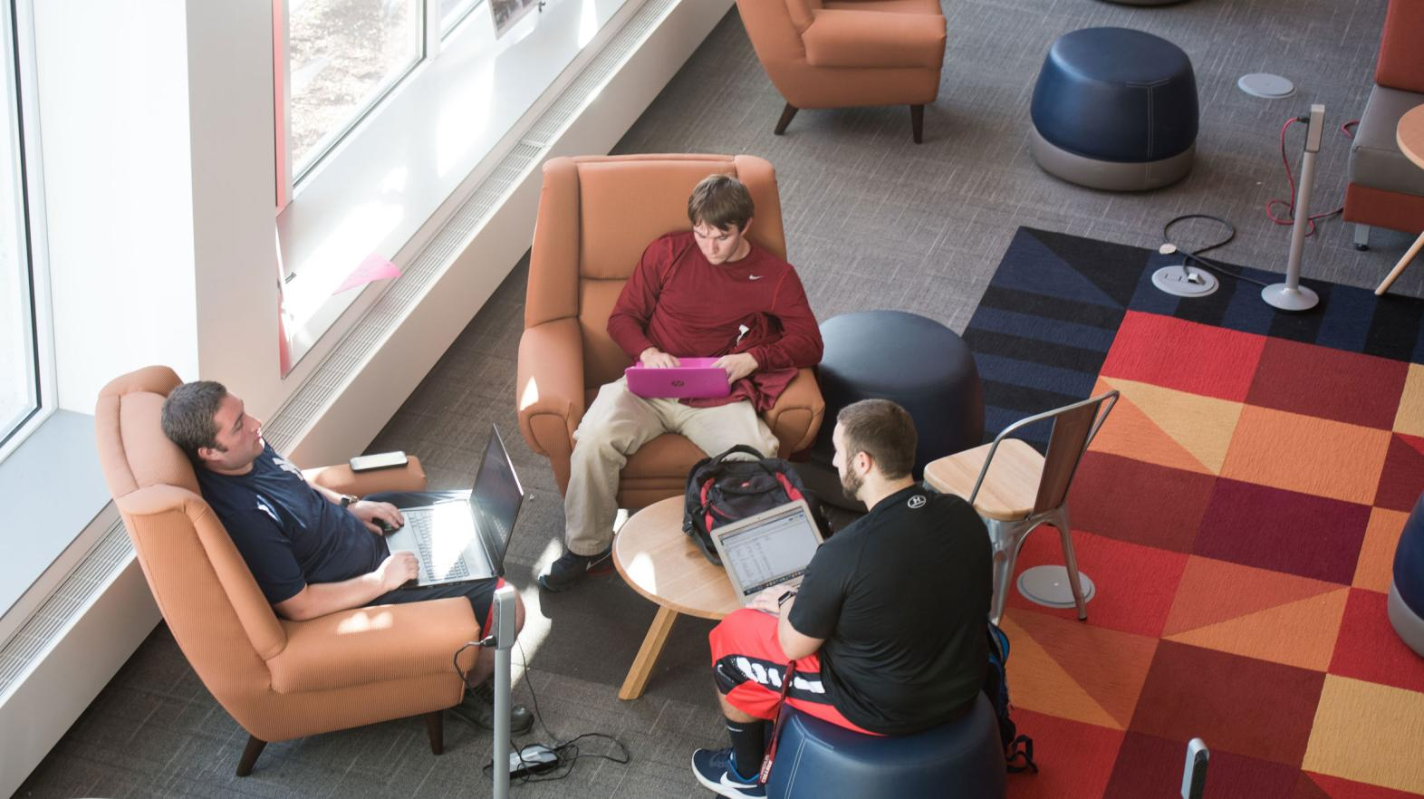 An overhead photo of three male students meeting in the Learning Commons.