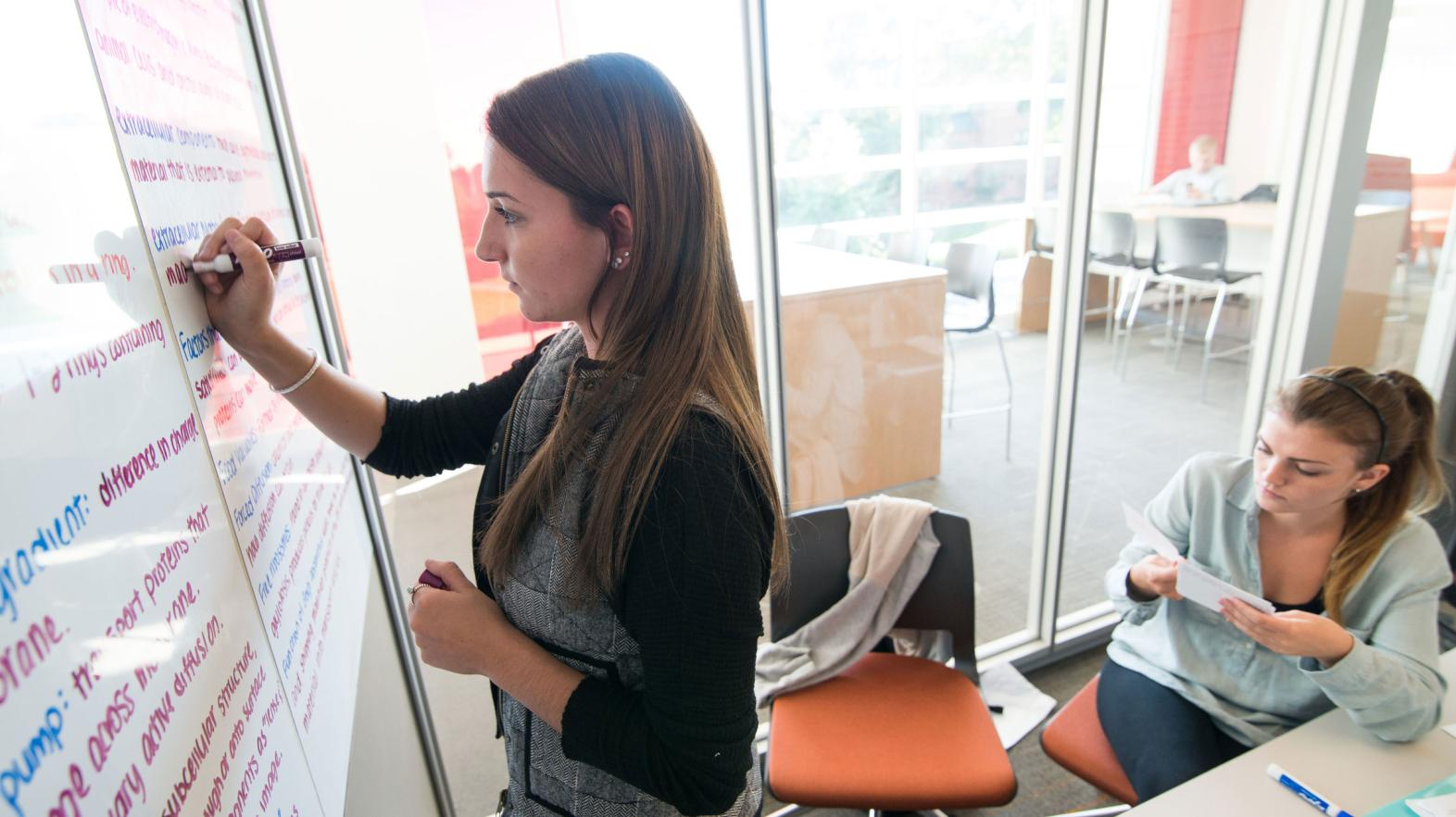 A female student takes notes on the white boards in the learning commons
